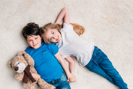 boy and girl lying on carpet with teddy bear at home and looking at camera