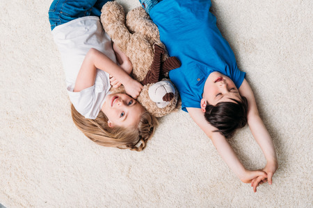 preadolescent: boy and girl lying on carpet with teddy bear at home and looking at camera
