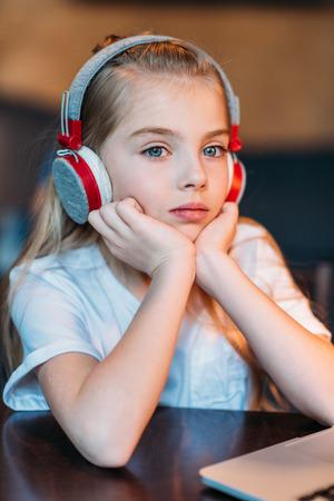 preadolescent: pensive little girl listening music in headphones Stock Photo