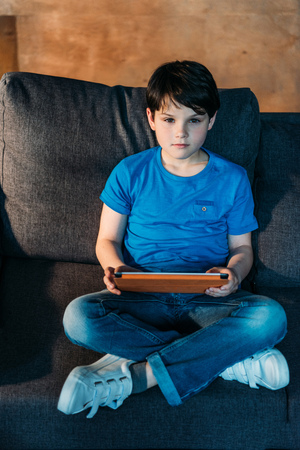 boy with digital tablet sitting on armchair and looking at camera Stock Photo