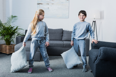 brother sister fight: little children in pajamas having pillow fight at home