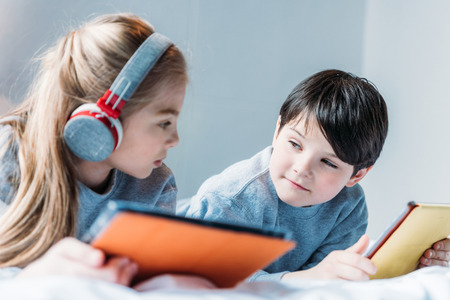 girl in headphones and boy using digital tablets while lying on bed