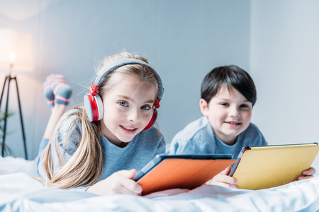 girl in headphones and little boy using digital tablets while lying
