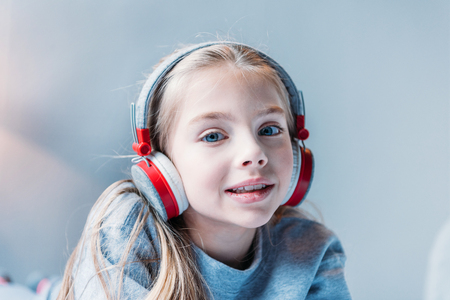 preadolescent: little girl listening music in headphones and looking at camera