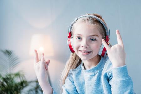 Lächelnd kleines Mädchen in Kopfhörer mit Rock-Zeichen Standard-Bild - 80649334