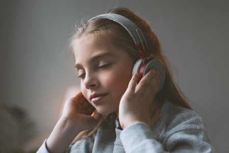 kid girl listening music in headphones with eyes closed Stock Photo