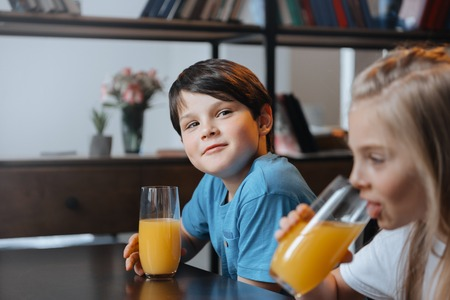 preadolescent: boy and girl drinking orange juice at kitchen together