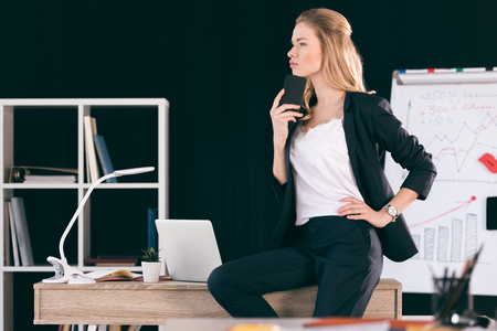 young businesswoman holding smartphone sitting on desk and looking away