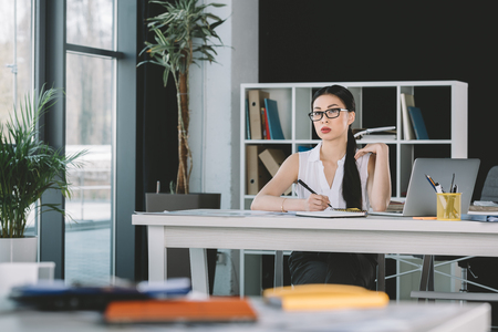 asian businesswoman working with laptop at workplace in office