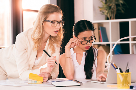 multiethnic businesswomen in formalwear looking at laptop at office