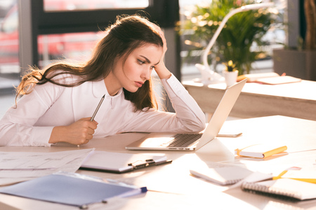 young businesswoman holding pencil and looking at laptop at workplace