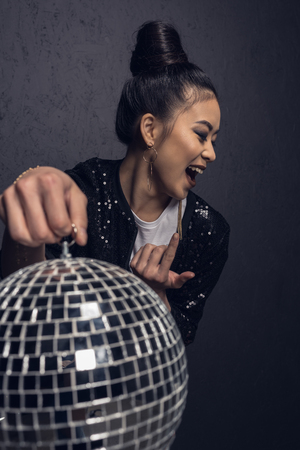cheerful asian girl with come here gesture holding disco ball in studio