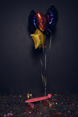 pink skateboard and colorful balloons on floor with confetti Banco de Imagens