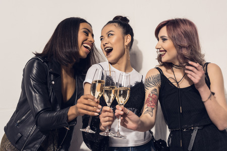 happy multiethnic girls drinking champagne at party