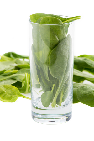 fresh green spinach leaves in glass isolated on white, ingredient for smoothie