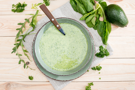 green creamy soup with fresh healthy ingredients on table