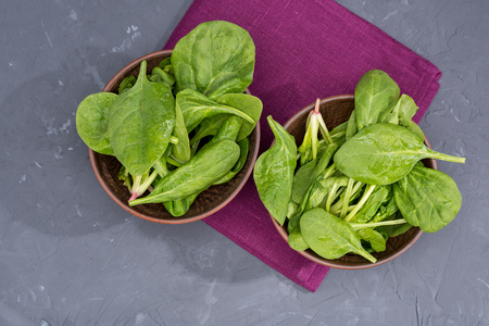 fresh green spinach leaves in bowls on napkin
