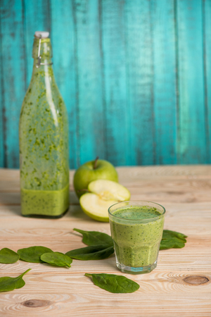 nourishing: apples with green leaves and smoothie in glass and bottle