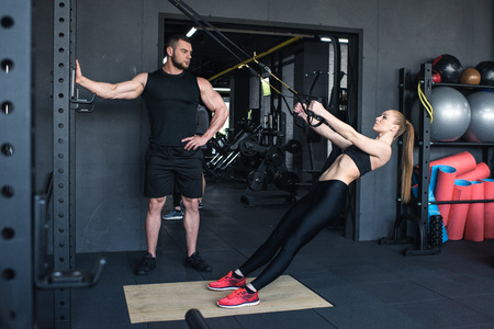 sportswoman training with trx resistance band while trainer looking at her Foto de archivo