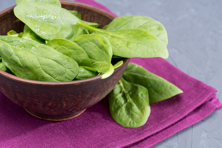 fresh spinach leaves in bowl on purple linen