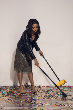 african american girl tidying up confetti with dust tray and broom