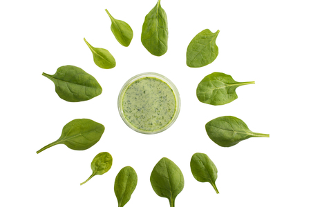 top view of green refreshing smoothie in glass standing in circle of spinach leaves Reklamní fotografie