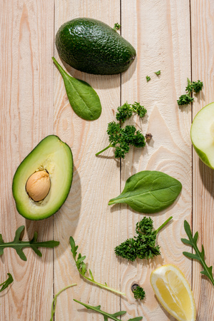 sliced avocado and fresh raw greens on wooden background Stock Photo