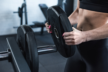 partial: athletic putting weight on dumbbell in gym