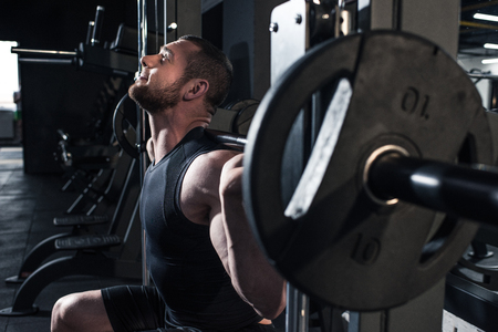 sportive man lifting barbell at gym