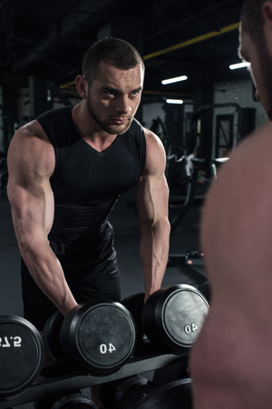 sportsman holding dumbbells while looking at reflection in mirror