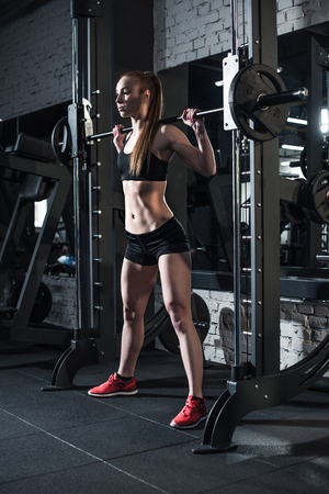 sportive woman lifting barbell at gym