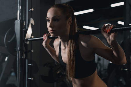 attractive sportswoman training with barbell in sports center