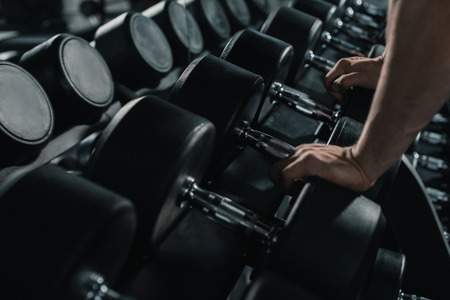 cross: muscular sportsman with big dumbbells in sports center Stock Photo