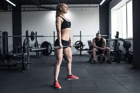 woman doing strength training with barbell while man sitting