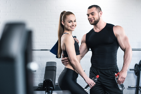 man in woman holding bottles of water and hugging in gym Stock Photo