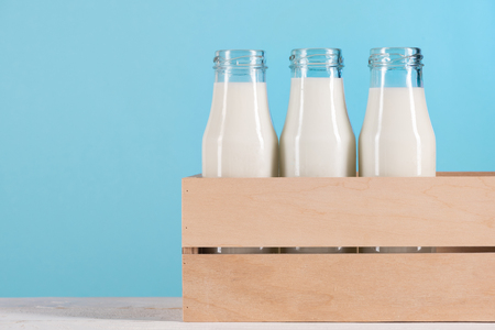 glass bottles with milk in wooden box on tabletop Фото со стока