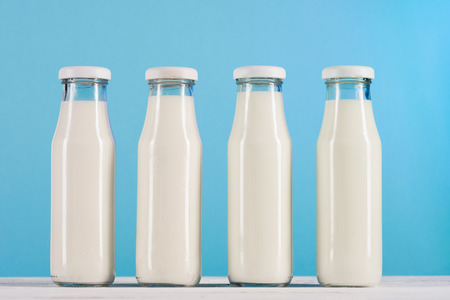 glass bottles with milk on tabletop at blue background