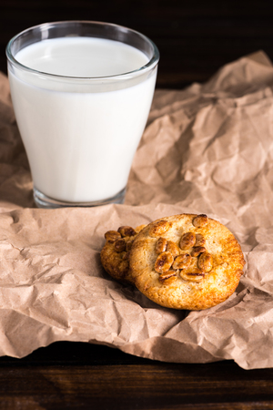 milk in glass and homemade cookies on baking paper