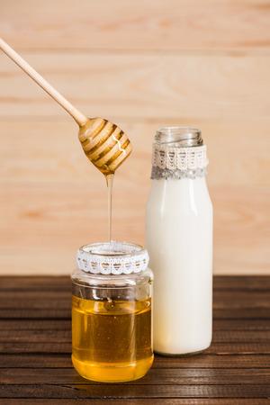 glass bottle of milk with honey in jar