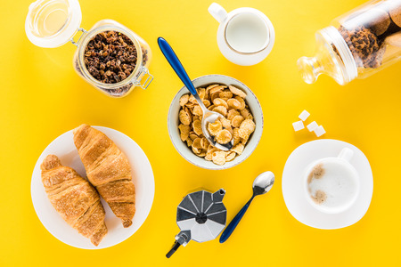 Top view of tasty breakfast with cereal flakes and croissants with coffee