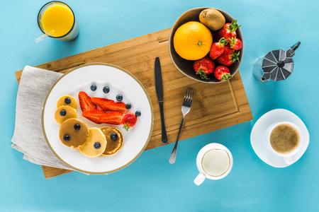 Vista superior de panqueques con bayas en el mostrador de la cocina con café y jugo de naranja Foto de archivo - 80724403