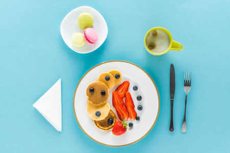 top view of pancakes with berries on plate with macarons on blue background