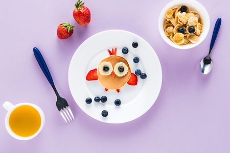 flat lay with creatively styled childrens breakfast on colorful tabletop