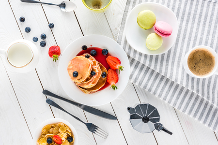 hotcakes: top view of pancakes with macarons and coffee with corn flakes on wooden tabletop Stock Photo