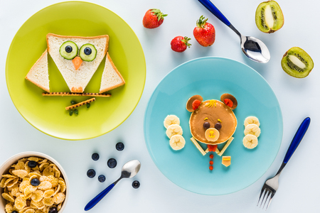 creatively: flat lay with creatively styled childrens breakfast with berries and kiwi on white