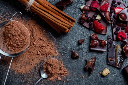 Pezzi di cioccolato al latte con noci e bacche con cannella e setaccio Archivio Fotografico - 80724732