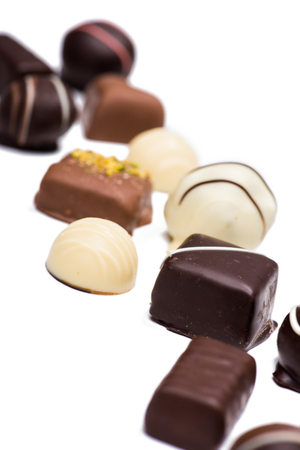 Close-up view of delicious assorted chocolate candies isolated on white