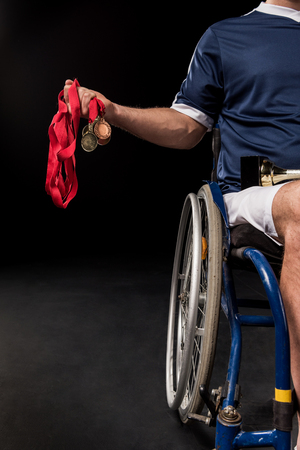 paraplegico: cropped view of paralympic sitting in wheelchair and holding gold medals isolated on black