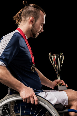 paralympic in wheelchair with gold medals on neck looking at champion goblet
