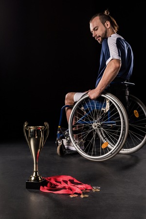 paraplegico: upset paralympic in wheelchair looking at champion goblet and gold medals